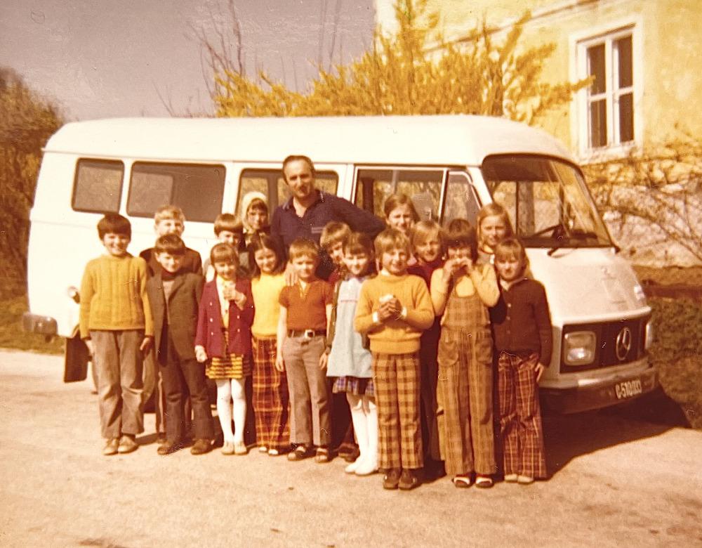 Schulbus, davor steht Franz mit einer größeren Anzahl an Schüler*innen. Inmitten steht Franzi.