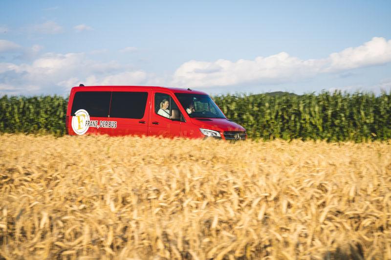 Franz, der Bus on Tour, im Vordergrund ist ein Weizenfeld zu sehen